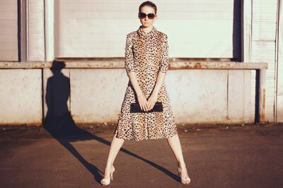 Woman in Animal Print Dress and Sunglasses